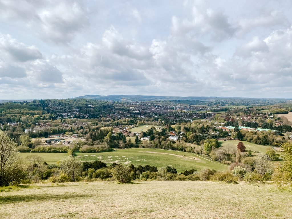 The green hillside of Box Hill gives way to views of Surrey and the South Downs in the distance