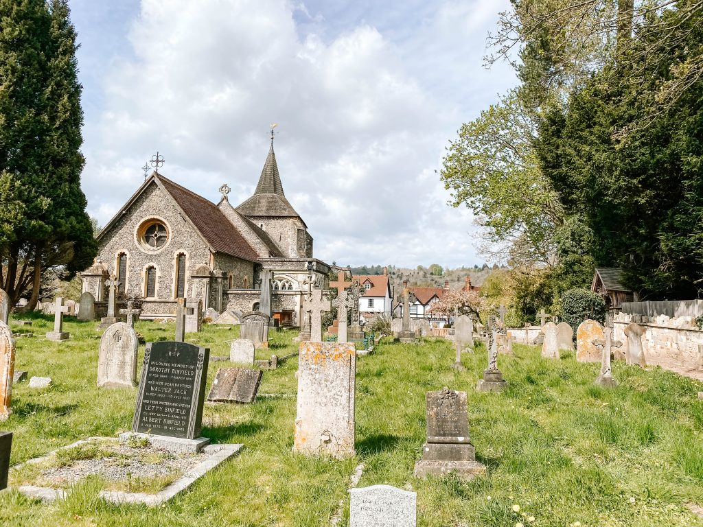 A view of the church in Mickleham across the churchyard with gravestones in the foreground