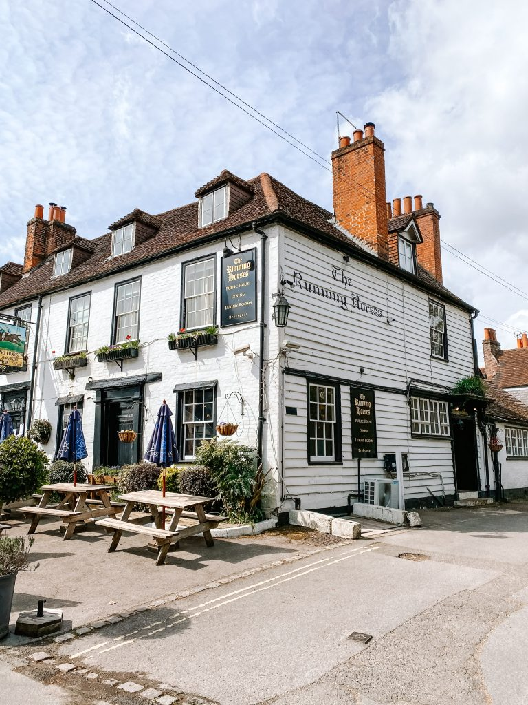 The Running Horses Pub, with white wood frontage and tables outside in Mickleham, Surrey