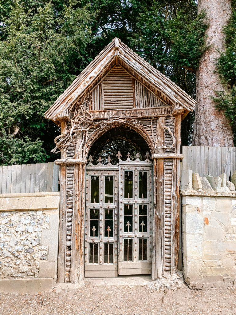 An old wooden gateway with carved patterns in Mickleham churchyard