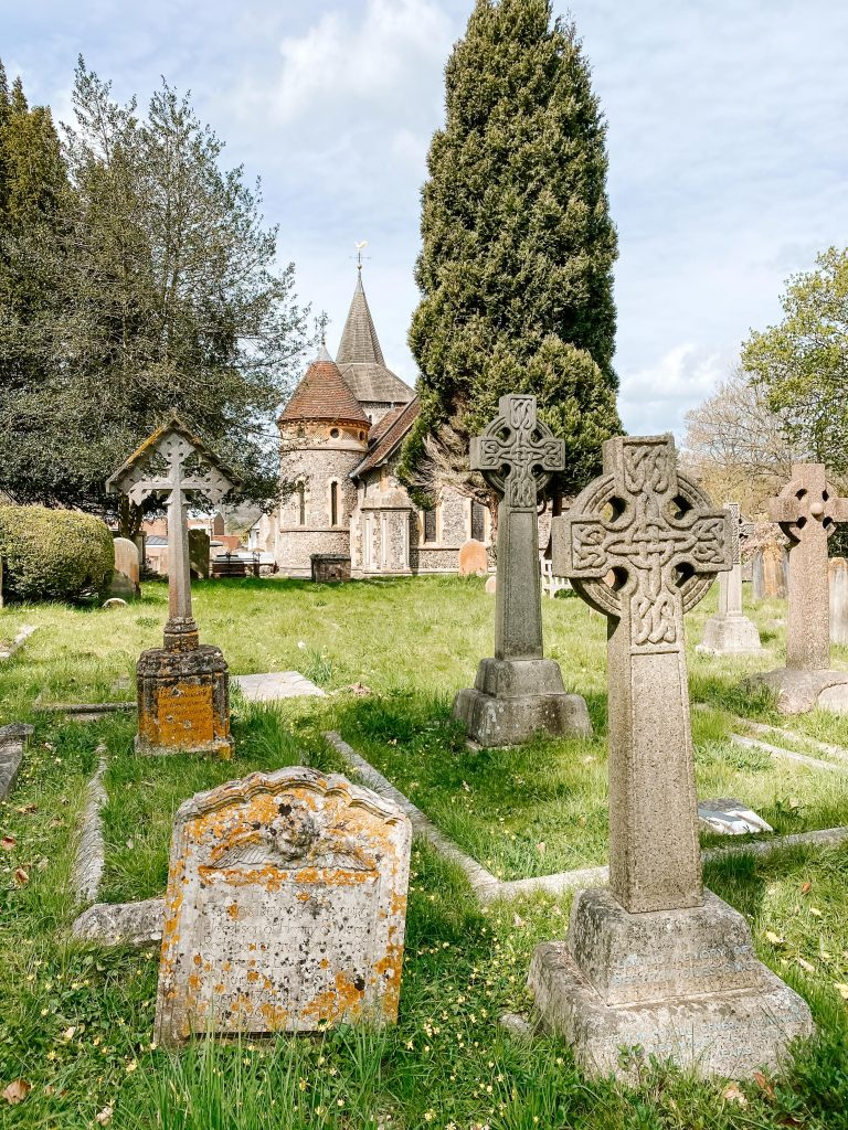 The churchyard in Mickleham with old celtic cross gravestones in the foreground and the church in the distance